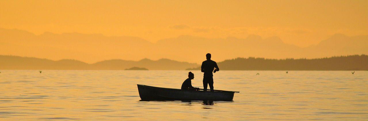 fishing on a lake during sunset