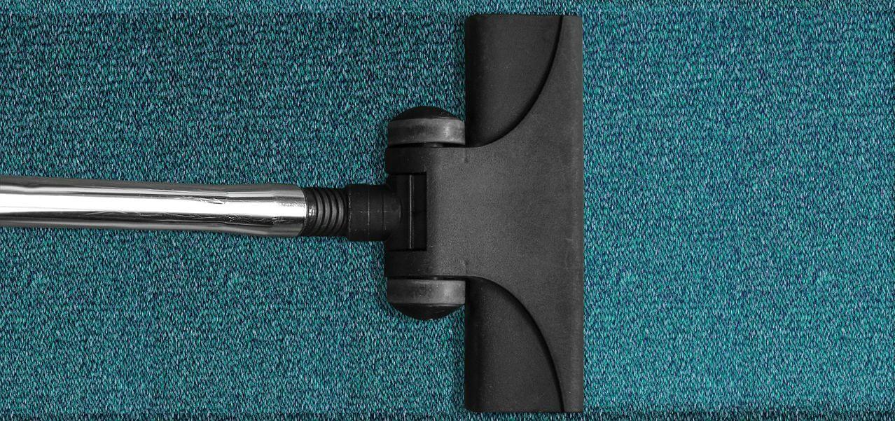 vacuum running along a blue carpet