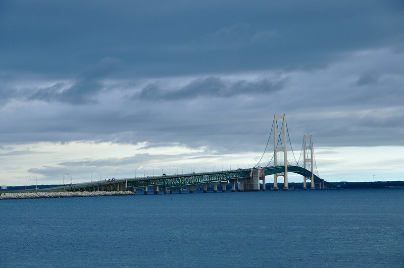 Mackinaw Bridge shown over water with a stormy sky
